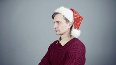 Displeased young man in santa hat looking at camera close up Stock Footage