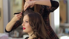 Professional hairdresser makes hairstyle for a long hair model. Close-up. Stock Footage