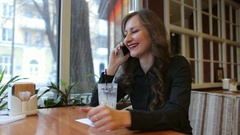 Young woman at cafe drinking coffee and talking on the mobile phone. Stock Footage
