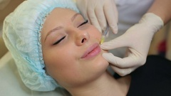 Close-up of hands of cosmetologist making botox injection to female lips. Stock Footage