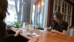Two young friends woman sitting in cafe, joking and laughing. Stock Footage