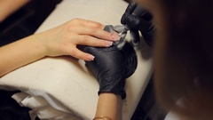 The master uses an electric machine to remove the nail polish on the hands. Stock Footage