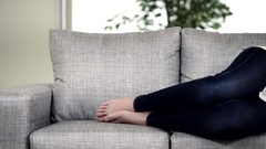 Young woman suffering from stomachache on sofa at home Stock Footage
