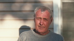 An ageing man with grey hair looking into camera, softly smiling. Rays of Stock Footage
