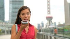 Businesswoman in Shanghai China talking on phone in Pudong financial district Stock Footage