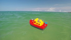 Red toy boat and sea Stock Footage