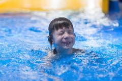 Happy child in pool at aqua park Stock Photos