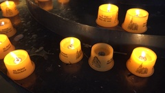 4K Closeup yellow candle burn in Munich cathedral spiritual ritual peaceful hope Stock Footage