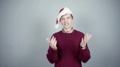 Young man in knitted sweater and santa hat talking about something at camera Stock Footage
