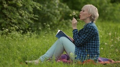 Young spring fashion woman blowing dandelion Stock Footage