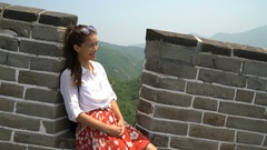 China travel at Great Wall - Woman sitting on the famous tourist attraction Stock Footage