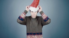 Young man in knitted sweater and santa hat puts on carnival costume details Stock Footage