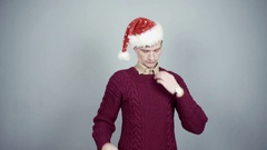 Young man in knitted sweater and santa hat entangled in flashing garland Stock Footage
