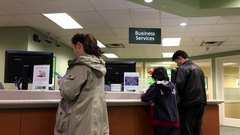 People at a business service counter talking to the teller inside TD bank Stock Footage