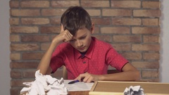 Child sitting at the desk holding flipchart with lettering idea on the Stock Footage
