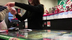 Woman paying cash for buying lottery ticket inside Save on foods store Stock Footage