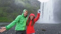 People by Skogafoss waterfall on Iceland waving saying hello having fun Stock Footage