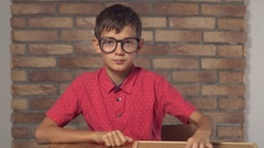 Child sitting at the desk holding flipchart with lettering it on the background Stock Footage