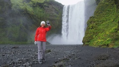Happy woman jumping excited by waterfall on Iceland waving hand Stock Footage