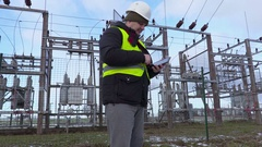 Electrician engineer using tablet near substation and walking away Stock Footage