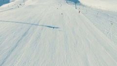 Several people ride ski by snow slope, view from ropeway in motion Stock Footage