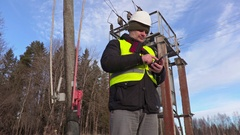 Electrician engineer using tablet near power lines and transformer Stock Footage