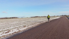 Hiker with hiking poles walking on the road in winter Stock Footage