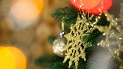 Baby's hands hanging small golden ball at Christmas tree branch in home interior Stock Footage