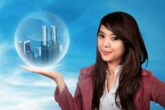 Asian woman holding building in sphere Stock Photos