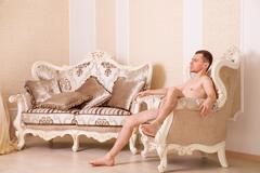 Naked macho man sitting on retro chair. Stock Photos