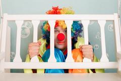 Punished clown sits under a bench. Stock Photos