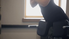 Woman black in training suit does hyperextensions exercises in gym Stock Footage