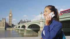 London woman on smart phone by Westminster Bridge - young business woman Stock Footage