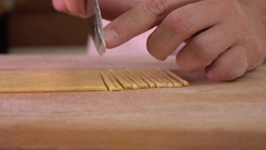 Man cutting homemade pasta with a knife. Amateur cooking at home. 4K close up Stock Footage