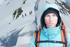 Climber man stands in winter mountains, Snowboarders walking uphill for freeride Stock Photos