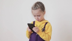 Little girl playing and touching a mobile phone Arkistovideo