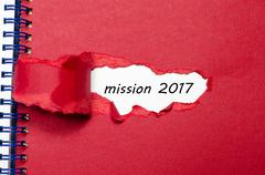 The word mission 2017 appearing behind torn paper Stock Photos
