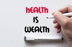 Health is wealth written on whiteboard Stock Photos
