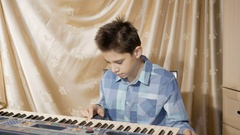 Happy boy teenager playing on an electronic piano, composes Stock Footage