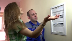 Female client needs professional help of electrician near circuit breaker box Stock Footage