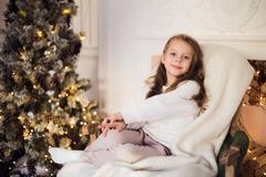 Little girl sitting on cozy wrapped in a blanket chair Christmas tree morning at Stock Photos