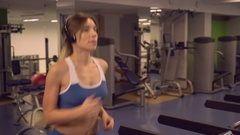 Lady run on training machine in sport club Stock Footage