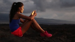 Woman using smart phone looking at fitness tracking app after running at night Stock Footage