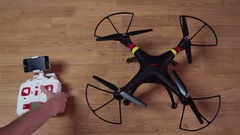 Woman takes a remote control drone Syma X8W includes blades, turns it off Stock Footage