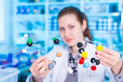 Woman scientist holding model of molecule or crystal lattice. scientist working Stock Photos