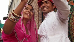 Couple in traditional Indian dresses taking a selfie on a mobile phone camera in Stock Footage
