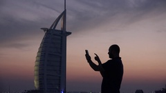 Dark silhouette of young man using tablet making photo in Dubai Burj al Arab 4K Stock Footage