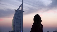 Woman silhouette back side view looking at Dubai Burj al Arab dusk twilight time Stock Footage