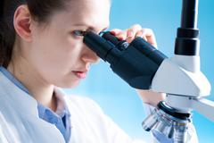 Young scientist studying new substance or virus in microscope.  Stock Photos