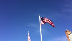 Pan tilt from United States flags to large U.S flag on side of building Stock Footage